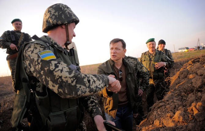 Oleh Lyashko, center, a lawmaker, who supported the protests that ousted Russian-leaning president Viktor Yanukovych and his government, shakes hands with a soldier on March 24 while visiting Ukrainian troops near Crimea, annexed by Russia, to support the Ukrainian soldiers' spirit. Ukraine's government ordered Ukrainian troops to pull back Monday from Crimea, ending days of wavering as Russian forces stormed and seized bases on the peninsula.