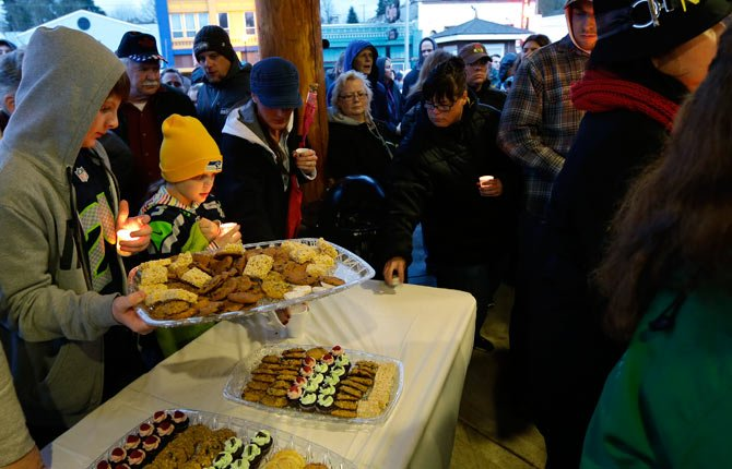 REFRESHMENTS ARE served as people gather March 25 at a candlelight vigil in Arlington, Wash., for the victims of a massive mudslide that struck the nearby community of Oso on Saturday, killing at least 16 people and leaving dozens missing.