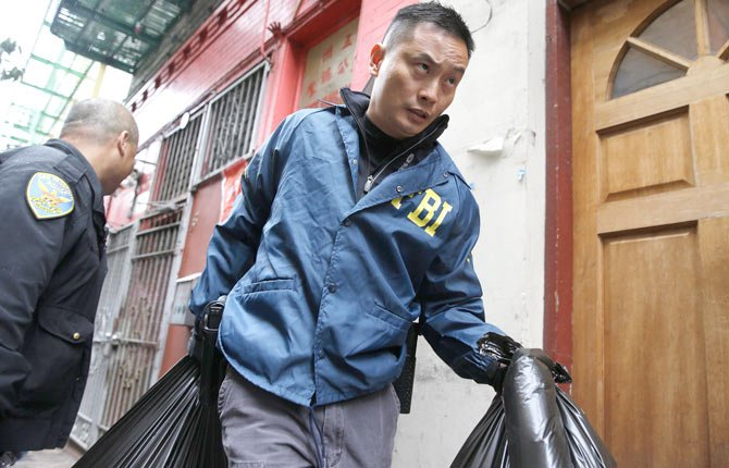 An FBI agent carries away bags of evidence following a search of a Chinatown fraternal organization Wednesday, March 26, in San Francisco. A California state senator was arrested Wednesday during a series of raids by the FBI in Sacramento and the San Francisco Bay Area, authorities said. An FBI spokesman confirmed the arrest of State Sen. Leland Yee, but declined to discuss the charges, citing an ongoing investigation.