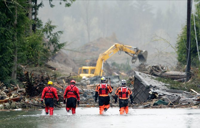 Four search and rescue workers wade through water covering Washington Highway 530 March 27 on the eastern edge of the massive mudslide that struck Saturday near Darrington, Wash., as heavy equipment moves trees and other debris in the background.