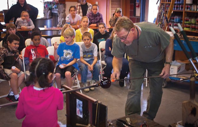 Andy Nichols, right, gets some volunteer assistance during a Northern Wasco County Park and Recreation District glass blowing event at Nichols Art Glass in The Dalles Wednesday afternoon. The glass blowing demonstration was just one of a number of events scheduled for the week of Spring Break.