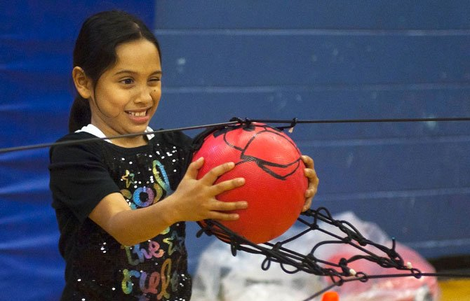 "Alicia takes aim with an ""angry birds"" ball March 28 in a slingshot-style catapult during a Northern Wasco County Parks and Recreation District event at St. Mary's Academy gymnasium over spring break."