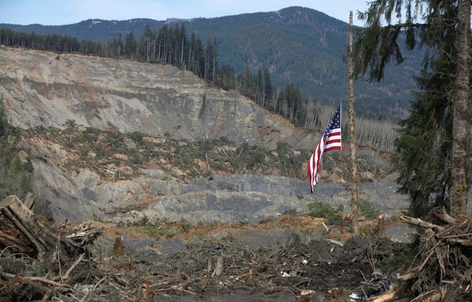 An American flag hangs at half-mast from the only cedar post left standing March 31 at the scene of a deadly mudslide in Oso, Wash.