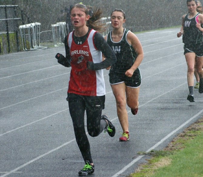 Columbia High sophomore Aidan Liddiard leads a pair of Woodland runners through the rain down the home stretch of the girls 1600-meter run last Thursday, during a 1A Trico League meet in Stevenson. Liddiard placed fifth in the race won by CHS senior Claudia Cortez in a time of 5 minutes, 51.43 seconds.