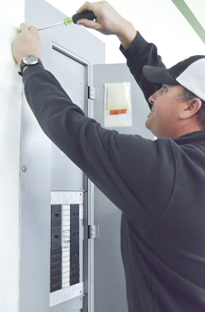 H2 Electric Owner Aron Hunsaker works on a fuse box to make sure the circuits are properly connected.