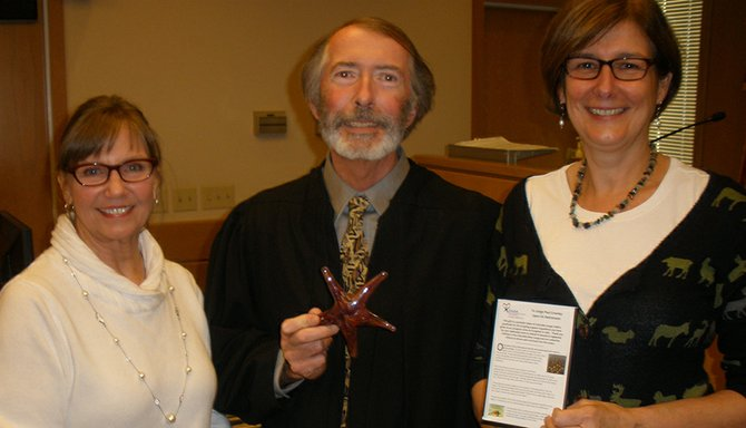 Judge Crowley accepts a glass starfish from Susan Erickson, CASA executive director, right, and Susan Baldwin, CASA volunteer manager.