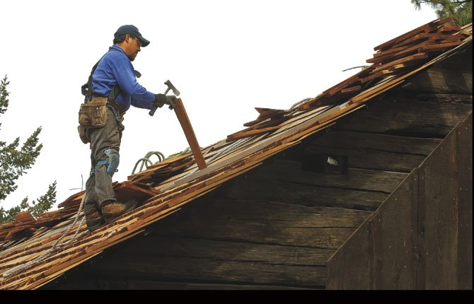 Jose Ibaira of Brown Roofing Company of The Dalles splits a shake to size as he replaces a roof on the Anderson Homestead barn at Fort Dalles Museum. Piled at his feet are a selection of shakes, which he sorts and splits for placement. The roof is being reconstructed as it was originally built, with the shakes nailed directly to the roofing slats, with no paper or plywood beneath. Half of the $12,685 project cost was funded through an Oregon Heritage Grant awarded by the Oregon Parks and Recreation Department (ORPD) and the Oregon Heritage Commission. The grant was matched by museum funds.