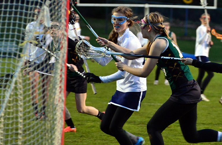 isabelle cullen weaves between two Cleveland defenders on her way to one of six goals she had in the Eagles' 15-9 win Tuesday.