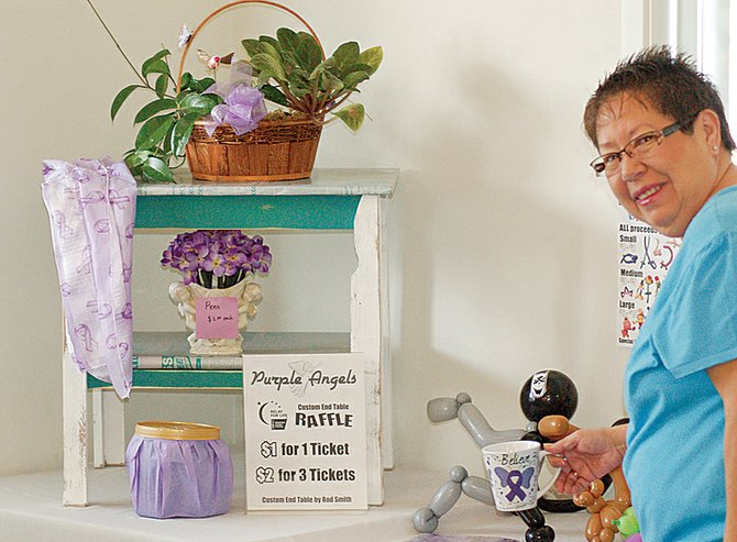 A custom end table made of recycled materials, as well as an assortment of other items are part of the fundraising efforts being made by the Daily Sun News Purple Angels Relay for Life team. Here, team member Mary Gomez helps arrange the display table of sale items.