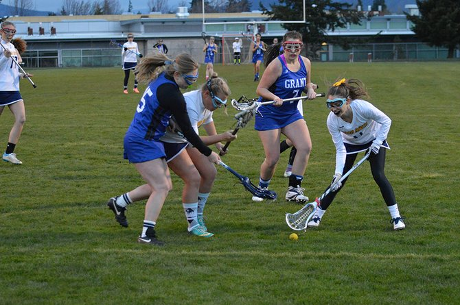 Ellery Hight, in white at far right, goes for a ground ball along with Hood River Valley teammate Lydia McElderry near the end of the first half of a Friday night game with the Grant Generals.