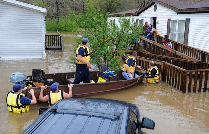 Firefighters rescue a family from their home, surrounded by floodwaters, in a mobile home park in Pelham, Ala., on Monday, April 7. Overnight storms dumped torrential rains in central Alabama, causing flooding across a wide area.