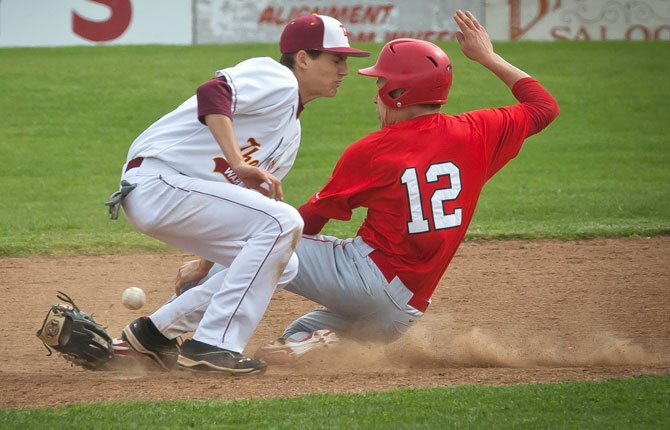 THE DALLES second baseman Colin Noonan loses control of the ball, and his glove, while trying for a tag on David Douglas junior Darrion Wedge in Saturday's game in The Dalles. The No. 4-ranked Eagle Indians won their fifth and sixth consecutive games over Glencoe and David Douglas.