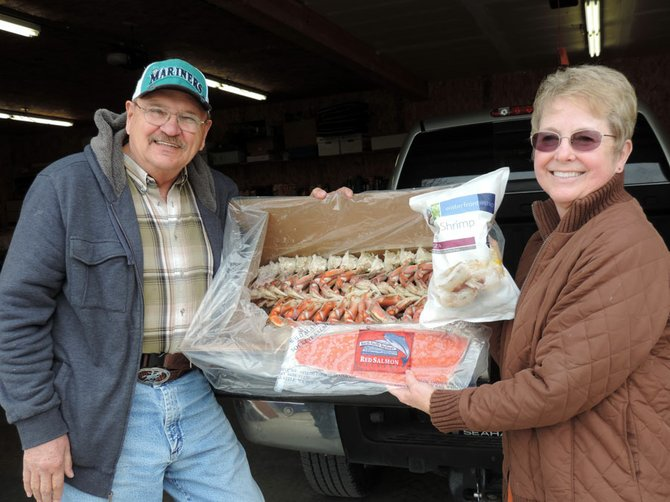 Larry and Jill Heming of Republic show off seafood won Sunday in a Bonaparte Snowmobile/ATV Club raffle.