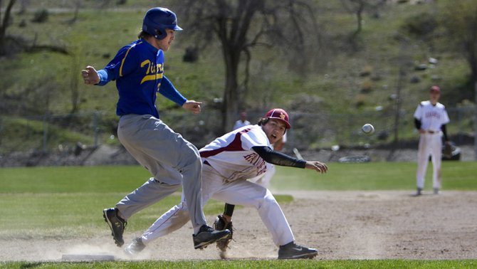 Tonasket's John Rawley reaches first base safely following an overthrow past Lake Roosevelt's Trey Nicholson on Saturday in Coulee Dam.