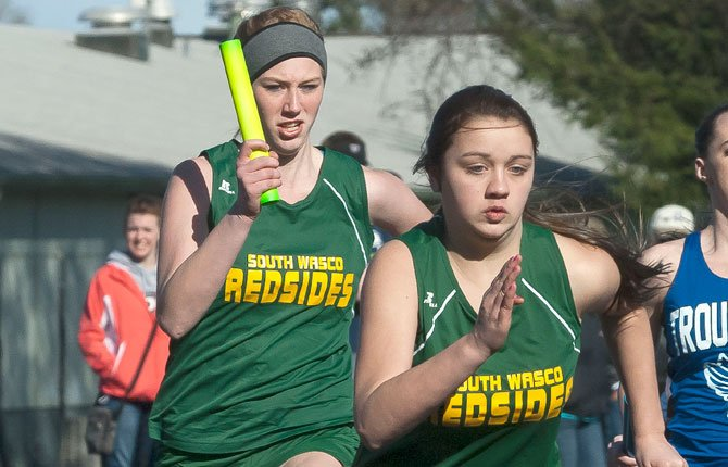 SOUTH WASCO'S Lindsey Hull (front) gets a quick start while partner Joy Kelly finishes her run in the 400-meter relay event. At the Tri-River Meet in Culver, the Redside girls finished in third place.