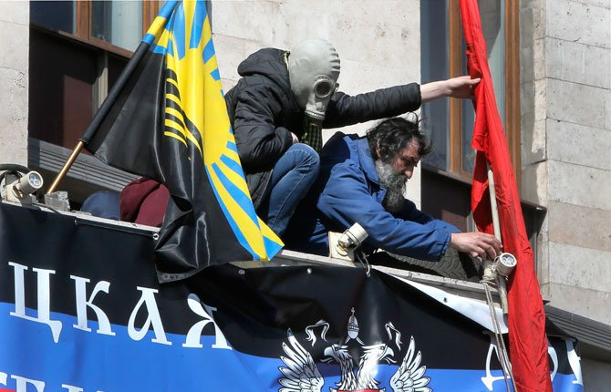 Pro-Russian activists set their flags over the entrance to the regional administration building in Donetsk, Ukraine, Tuesday, April 8. Ukrainian authorities on Tuesday reasserted control over an administration building in the country's second-largest city of Kharkiv, 250 Km ( 155 miles) north of Donetsk, which had been seized by pro-Russian protesters, and authorities detained some dozens.