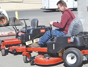 Easing a lawnmower into place for an outdoor display is Jim Grubenhoff of Harold's Repair and Rental. Many riding mowers now offer a tight turn radius for smoother maneuvering around trees and other obstacles.