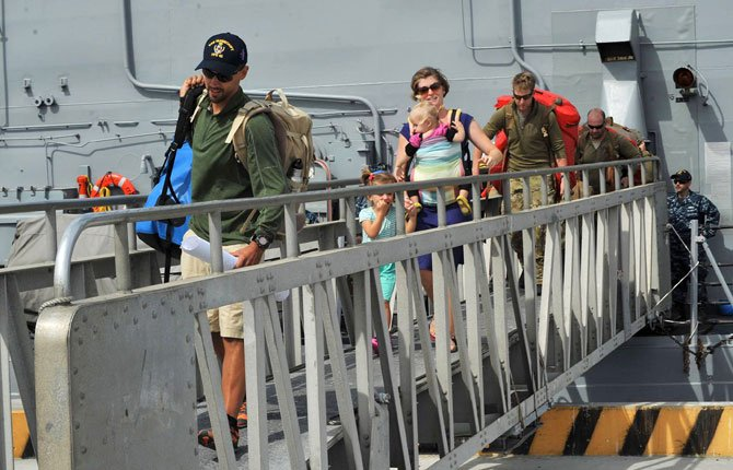 The Kaufman family disembarks from the USS Vandegrift on April 9 at Naval Air Station North Island in San Diego, following their rescue at sea three days earlier. Six days after the family of four found themselves helpless and adrift in a sailboat far into the Pacific with a vomiting and feverish 1-year-old aboard, a Navy warship delivered them safely to shore, where they had begun their attempted around-the world voyage before the child was born.