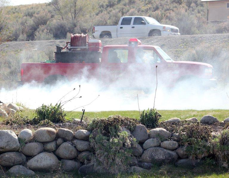 Riverside firefighters monitor a small brush fire set Thursday by a town homeowner to clear weeds along Kendall Road.