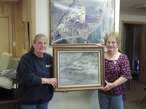 Jean Hanel, left, and Janet Princehouse hold a 1940s aerial photo of the upper mill property, under construction, as they stand in front of a similar photo of the lower mill property, c. 1990s.