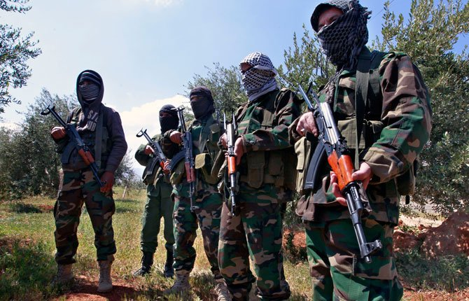 Hezbollah fighters stand guard at the Lebanon-Syria border April 13, near the northeastern Lebanese town of al-Qasr, Lebanon. The Shiite group has sent hundreds of its fighters into Syria to shore up President Bashar Assad's overstretched troops, helping them gain ground around the capital, Damascus, and near the Lebanese border.