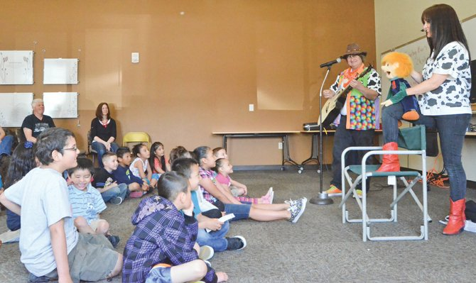 Cowboy Buck and Elizabeth, along with their 'son', Peter, perform at this past Saturday's spring party at the Grandview Library. The musical entertainers performed a number of their songs for those attending the event.