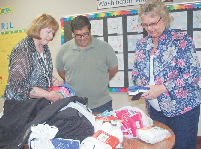 Washington Elementary School's Diego Alvarez (C) admires the piles of sweatpants, underwear and socks given to the school counselor for use by students who may need emergency change of clothes.  Making the donations are Joanne Vining (L) and Lois Olson (R), representing the Yakima County Chapter of Thrivent Financial, a non-profit Christian based volunteer organization.