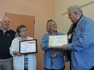Marilyn Wall accepts her 30-year awards from Bill Ensign of AARP. Tax-Aide clients and volunteers looked on during a brief ceremony at Hood River County Library in Hood River.