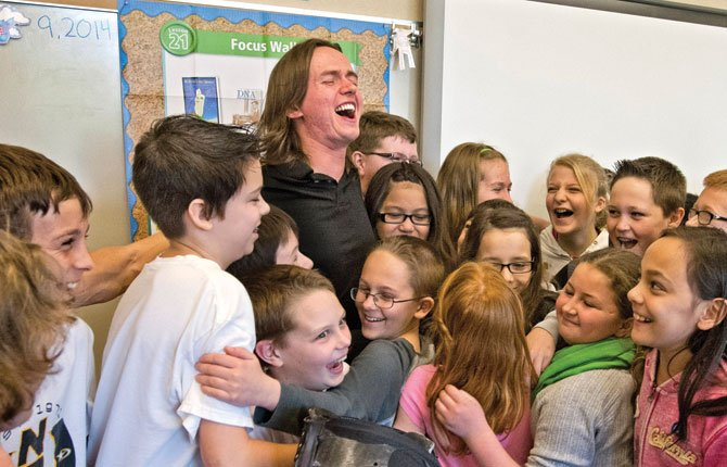 Children surround marathoner Edward Lychik after he gave an inspiring talk April 9 to fifth and sixth graders at Maplewood Elementary School in Puyallup, Wash.  The combat veteran's left leg had been amputated at the hip socket, and doctors had told him if he walked again, it would be on crutches. Lychik ignored that diagnosis and kept talking to his physical therapist, Alicia White.