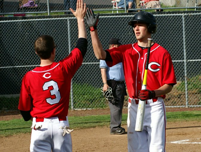 Dawson Reynier offers Jared Garwood a high five after Gar-wood scored the go-ahead run in game one of a Trico League baseball double-header between Columbia High and Kalama on April 8. Garwood led CHS to a 7-3 win, going 3 for 3 with two runs batted in.