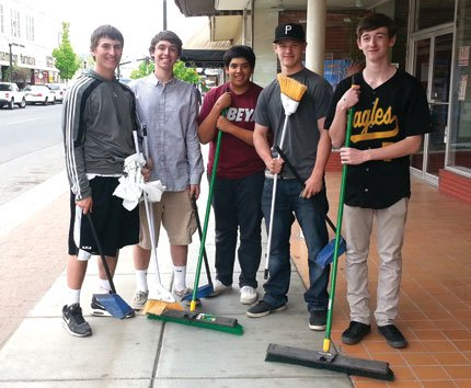 Students, from left, Colton Walker, Dylan DesRochers, Boston Bate, Devin Wilson and Riley Twidwell took brooms in hand Wednesday at the downtown clean-up day organized by The Dalles Main Street.