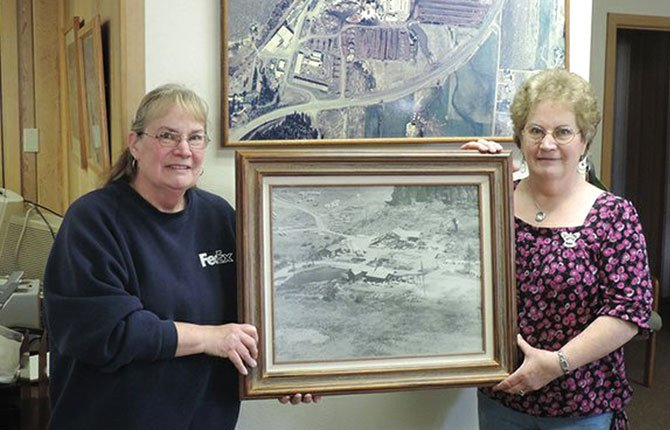 Jean Hanel, left, and Janet Princehouse hold a 1940s aerial photo of the upper mill property, under construction, prior to the April 11-12.