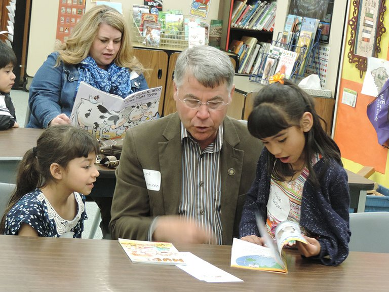 Yulisa Chavez, left, and Noelia Bastian, Westside Elementary first graders, read with Chuck Thomsen during Friday's Start Making A Reader Today (SMART) event at the school. Behind Thomsen is Stephanie Serak of Walmart.