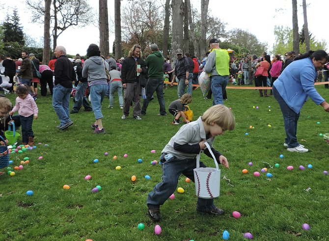 "Kaden Michaud, 4, collects Easter eggs, shortly after a ""secret egg layer"" passed by, following the frantic first wave of egg-hunters."