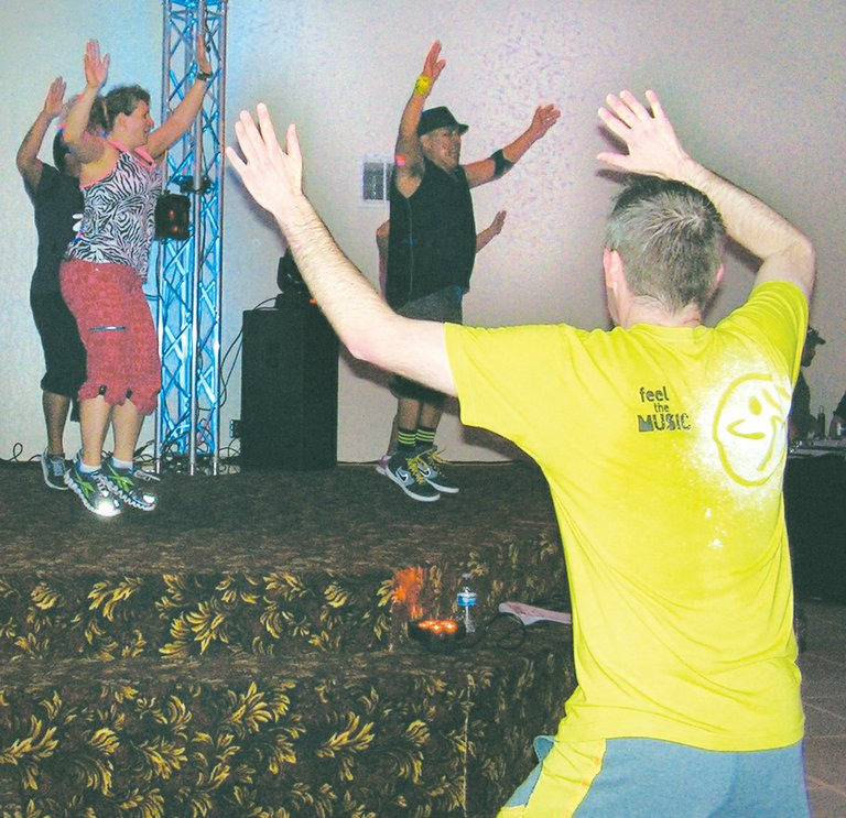 An estimated 50 people turned out for a Zumba fundraiser event last night, Tuesday, at Grandview's Reale Hall to benefit next month's Relay for Life. Organized by the Yakima Valley Farmworkers Clinic, the event offered participants like Henry Stamschror (pictured in the foreground with back to camera) an opportunity for a Latin-style exercise class. The festive evening also featured door prizes, a light show and a DJ. The Zumba class was led by instructors (L-R in the background) Charlotte McNair and Carlos Trevino, along with Juan Lares and Cheyenne Ammerman.