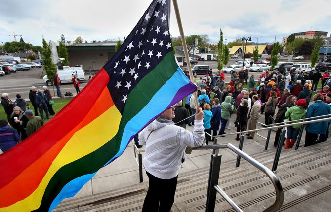 TERESA SHELLEY waves a rainbow-colored American flag on the steps of The Wayne L. Morse United States Courthouse April 22 in Eugene  during a vigil in support of gay marriage sponsored by Oregon United for Marriage. The advocacy group staged similar vigils in seven cities across Oregon on Tuesday evening, a day before oral arguments are to be delivered in U.S. District Court calling for an end to the ban on same-sex marriage in Oregon.