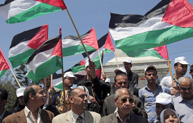 Palestinians wave their national flags during a rally to demand the end of Palestinian political divisions, at the main square of Gaza City, in the northern Gaza Strip, Tuesday, April 22. Palestinians have been divided since 2007 when Hamas took control of the Gaza Strip from forces loyal to Palestinian President Mahmoud Abbas of Fatah. Since then Hamas rules Gaza while Abbas governs some areas in the West Bank. Several attempts at reconciliation failed.