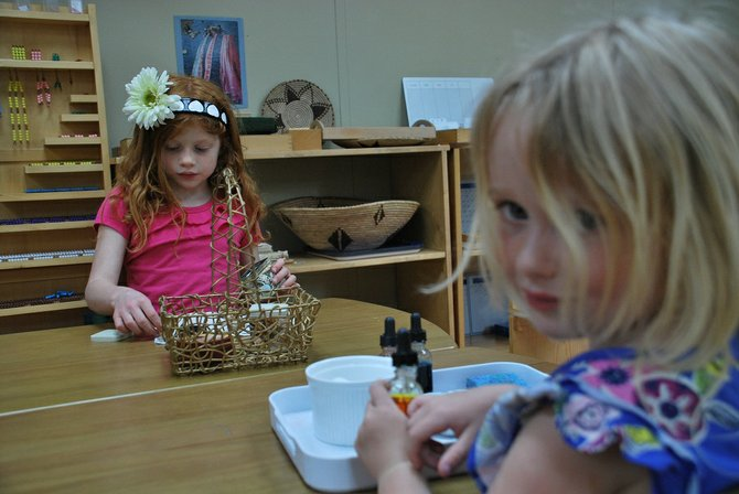 Charlotte Irwin sorts shells while her friend, Sylvia Perrin, works on mixing colors in the Children's House at Little Oak Montessori School. The School plans on expanding for the next school year after seeing an increase in interest and enrollment this year.