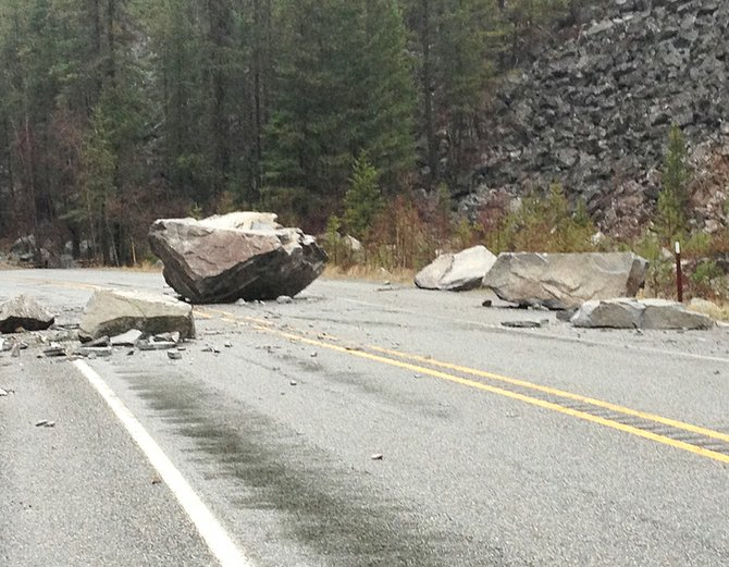 A boulder and several smaller rocks sit on state Highway 155 this morning.