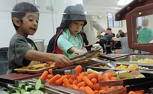 Students use tongs at the school's salad bar.