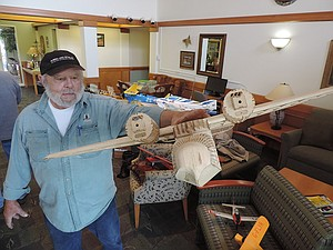 Aeromodelers club member Al Hawkins holds model of Grumman Goose, without the fuselage, one of about 40 planes on display.
