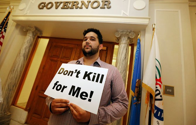 HOSSEIN DABIRI with Oklahoma Coalition Against the Death Penalty holds a sign protesting the death penalty at the State Capitol in Oklahoma City April 29. Oklahoma prison officials halted the execution of an inmate after the delivery of a new three-drug combination on Tuesday failed to go as planned.