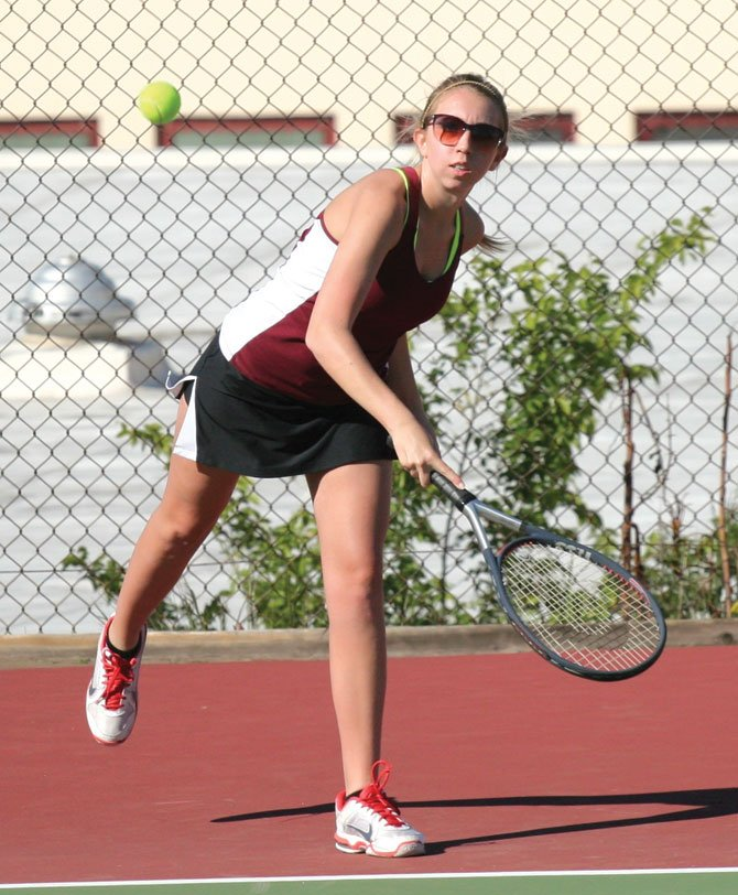 THE DALLES tennis player Brittany Watkins gets off a serve in her doubles match  Wednesday in Hood River, Watkins and doubles partner,  Rebekah Kohltfarber, won their match to lead the Tribe to a 5-3 league win.