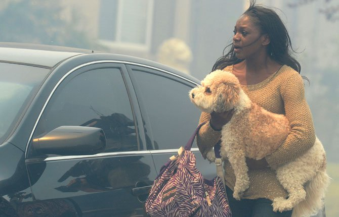 A WOMAN who is evacuating her home carries a dog to a vehicle in smoke from the Etiwanda Fire in Rancho Cucamonga, Calif., April 30. The wildfire driven by surging Santa Ana winds sent a choking pall of smoke through foothill neighborhoods, forcing the evacuation of at least 1,650 homes and the closure of at least seven schools. The fire was reported about 8 a.m., grew to 200 acres by noon, quadrupled in size within a few hours and continued to grow as it roared through dry brush.