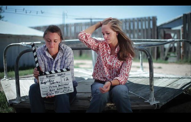 MAGGIE HANNA, left, and her younger sister Emy play with a clapboard during one of many filming sessions for the Hanna Ranch documentary that was six years in the making.	Contributed photo