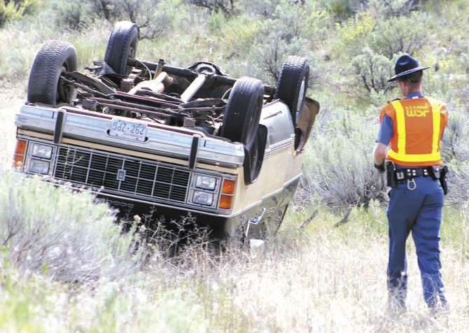 A Washington State Patrol trooper investigates the crash scene where the vehicle of Sandra J. Cohen, 61, of Omak, overturned Friday two miles north of the city.