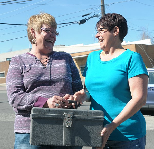 Holly Cox (left) takes the tool chest for Windshield Magic from Shanna Caba (right).