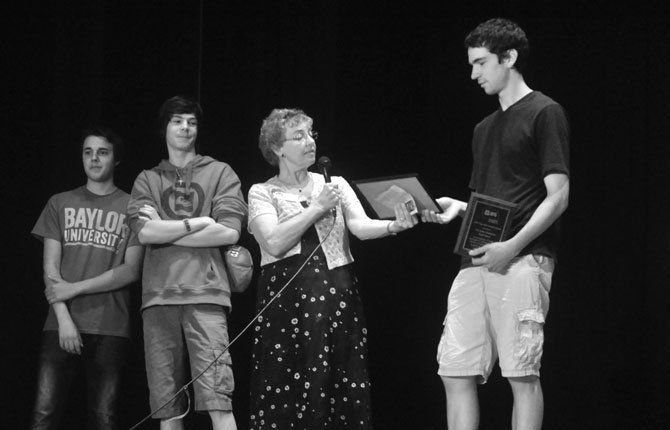 AFS Exchange students (from left) Rocco Cozza of Italy and Xavier Michel of Switzerland look on as The Dalles AFS Chapter Chair Rymmel Lovell presents a 2014 AFS Top School Award to TDHS ASB President Cole McDowell.