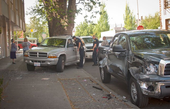 Officers investigate a two-vehicle motor vehicle accident at Fifth and Washington Streets in The Dalles which left one vehicle on the sidewalk and badly damaged another Tuesday afternoon.  A driver was cited for careless driving and driving uninsured.