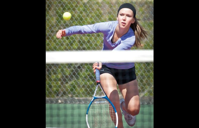 SHERMAN'S Meghan Belshe lunges forward for a return shot in her singles match this season in Moro. Tuesday, Belshe won her match, 8-6.